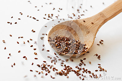 Coriander and flax seeds pouring into wooden spoon