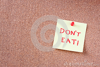 Cork board with pinned yellow note and the phrase dont eat written on it. room for text.