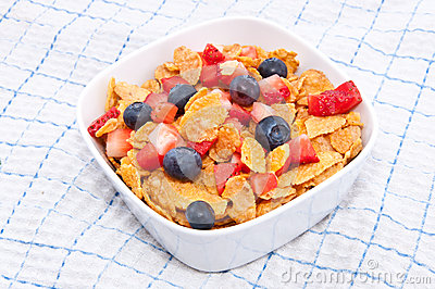 Cornflakes with fresh fruits on a tablecloth