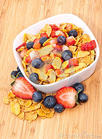 Cornflakes with fruits on wood
