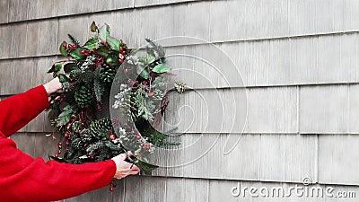A coroa de Natal caseira é colocada pelas mãos de uma mulher de camisa vermelha que a pendura na parede exterior da casa filme