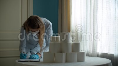 Coronavirus panic buying. Young woman counting toilet paper stocks and makes notes on a piece of paper. Covid-19 pandemic stock footage