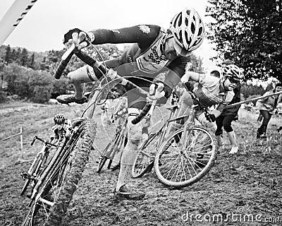 Corredores de sexo masculino de Cycloross en el fango Foto editorial