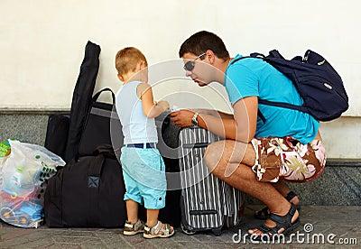 Corsa del figlio e del padre con bagagli enormi