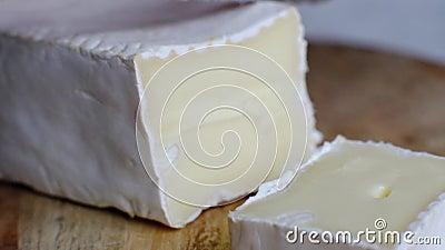 Cortando o queijo macio, o brie francês ou o camembert, tiro macro filme