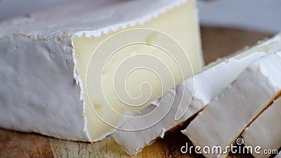Cortando o queijo macio, o brie francês ou o camembert, tiro macro video estoque
