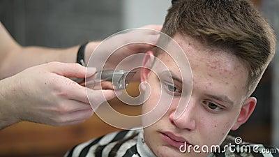 Corte de pelo de joven en Barbershop Cierre del cabello de recorte maestro con pinza almacen de video