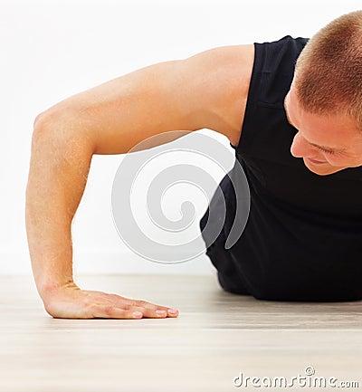 Corte la imagen de un hombre joven que hace un pushup