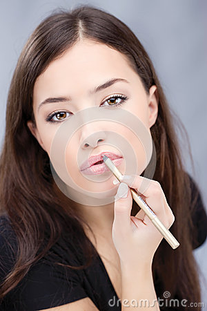 Cosmetic pencil on woman s lips, focus on lips