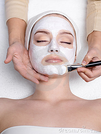 Cosmetician apllying mask on face of woman