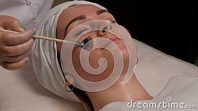 Cosmetologist fêmea que mancha o tratamento cosmético na cara do ` s do cliente no centro da cosmetologia Menina bonita durante filme