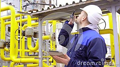 Costruisca la tenuta della compressa, parlante sul walkie-talkie in fabbrica industriale moderna archivi video