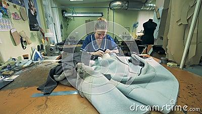 A costureira está costurando casacos de pele em uma oficina filme