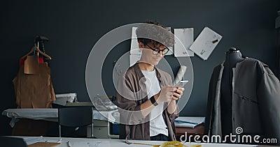 Costureira moderna que usa o smartphone no sorriso texting da tela de toque do trabalho vídeos de arquivo