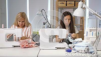 Costureiras no trabalho na oficina que costuram a roupa perto da máquina de costura, vista dianteira vídeos de arquivo