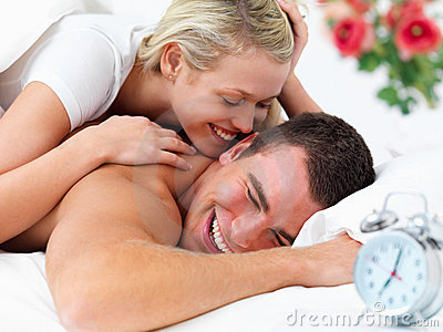 Cosy couple lying in bed together