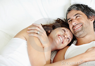 Cosy mature couple smiling on bed