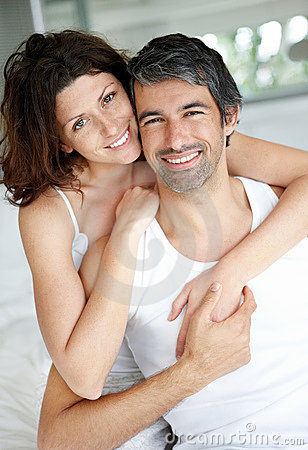 Cosy middle aged couple relaxing in bedroom