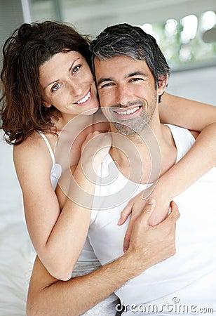 Cosy mittlere gealterte Paare, die im Schlafzimmer sich entspannen