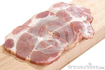 Cou cuit découpé en tranches de porc sur un panneau de découpage