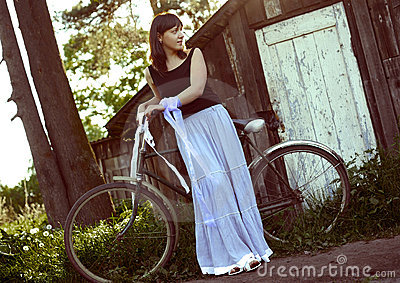 Woman with bicycle near old house