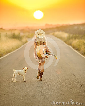 Country girl walking down a sunset road