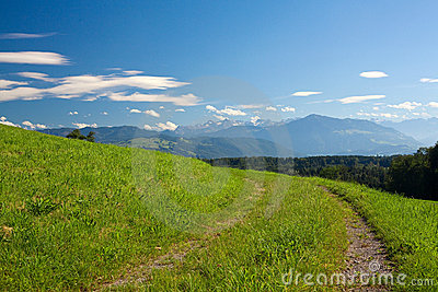 Countryside road, green field, mountains