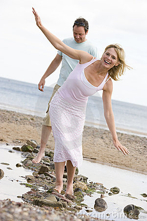 Free Couple At The Beach Walking On Stones And Smiling Royalty Free Stock Photos - 5931628