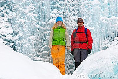 Couple backpackers and ice waterfall