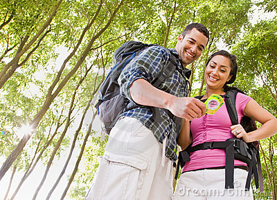 Couple in backpacks looking at compass