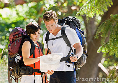 Couple with backpacks and map