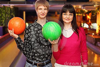 Couple with balls stand in bowling club