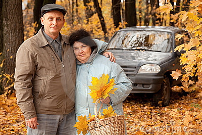 Couple with basket of maple leaves near black car