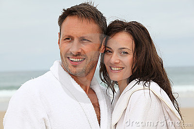 Couple in bathrobe at the beach