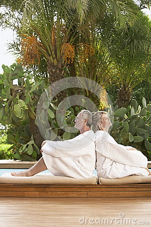 Couple In Bathrobes Sitting Back To Back By Pool