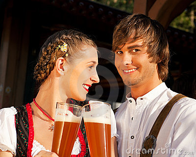 Couple in Bavarian Tracht clinking glasses