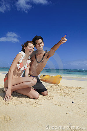 Couple on the beach in hawaii pointing