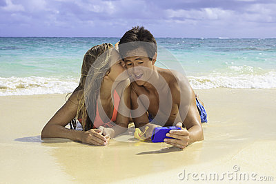 Couple on the beach photographing
