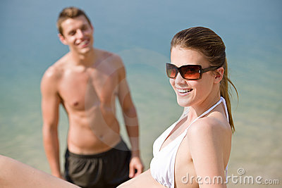 Couple on beach - sunbathing in swimsuit by sea