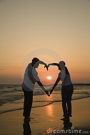Couple on beach at sunset.