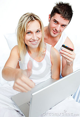 Couple in bed buying on-line with thumb up