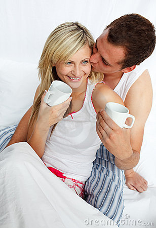 Couple in bed drinking coffee with affection