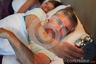Couple In Bed With Man Reaching To Switch Off Alarm Clock