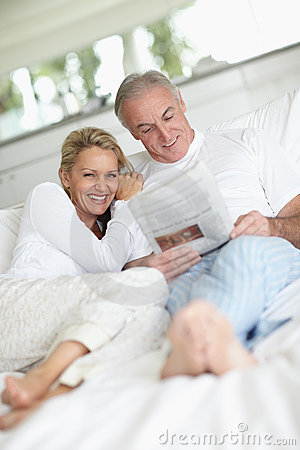 Couple in bed reading the newspaper together