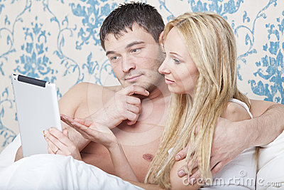 Couple in bed with tablet computer