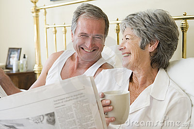 Couple in bedroom with coffee and newspapers