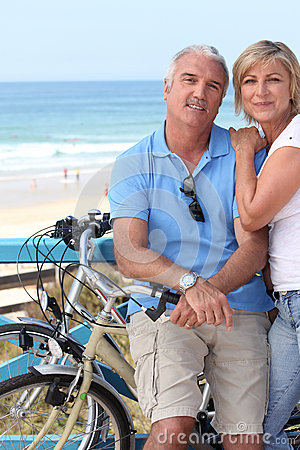 Couple biking by the seashore.