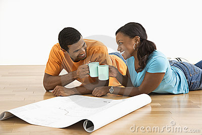 Couple with blueprints toasting.