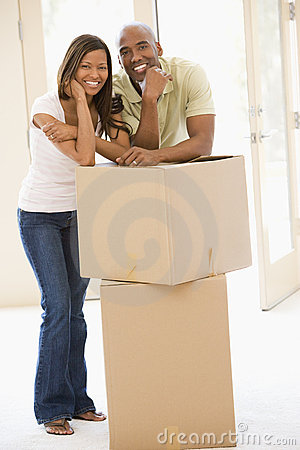 Couple with boxes in new home smiling