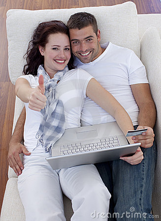 Couple buying online at home with thums up